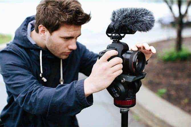 Man setting up camera with shotgun mic attached to top