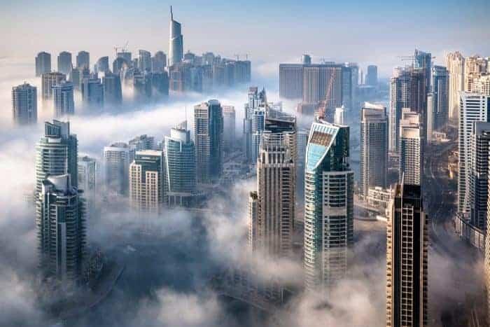 An impressive aerial top view of the Dubai Skyline on a foggy day.