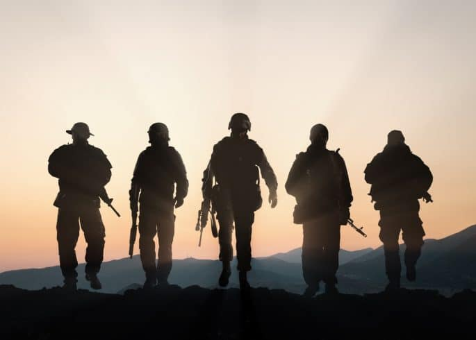 Military silhouettes of soldiers against the backdrop of sunset sky.