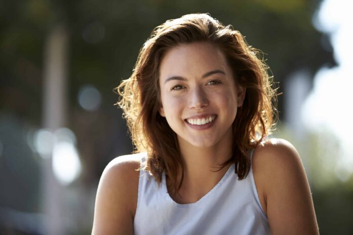 Outdoor Portrait Photography Tips - Head and shoulders of young woman sitting outdoors