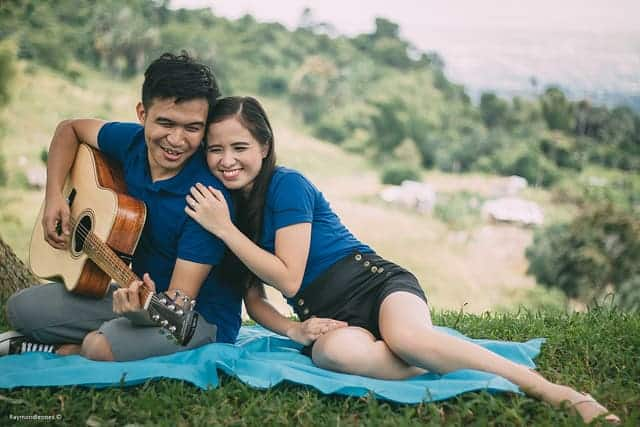 couple sitting in the ground leaning to each other with guy playing a guitar