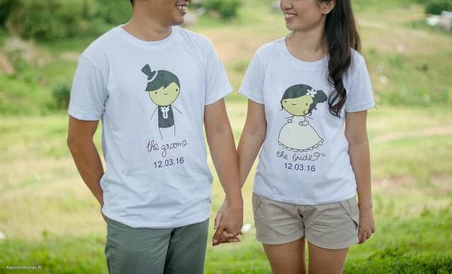 couple holding hands with a field as their background and their upper faces are unseen