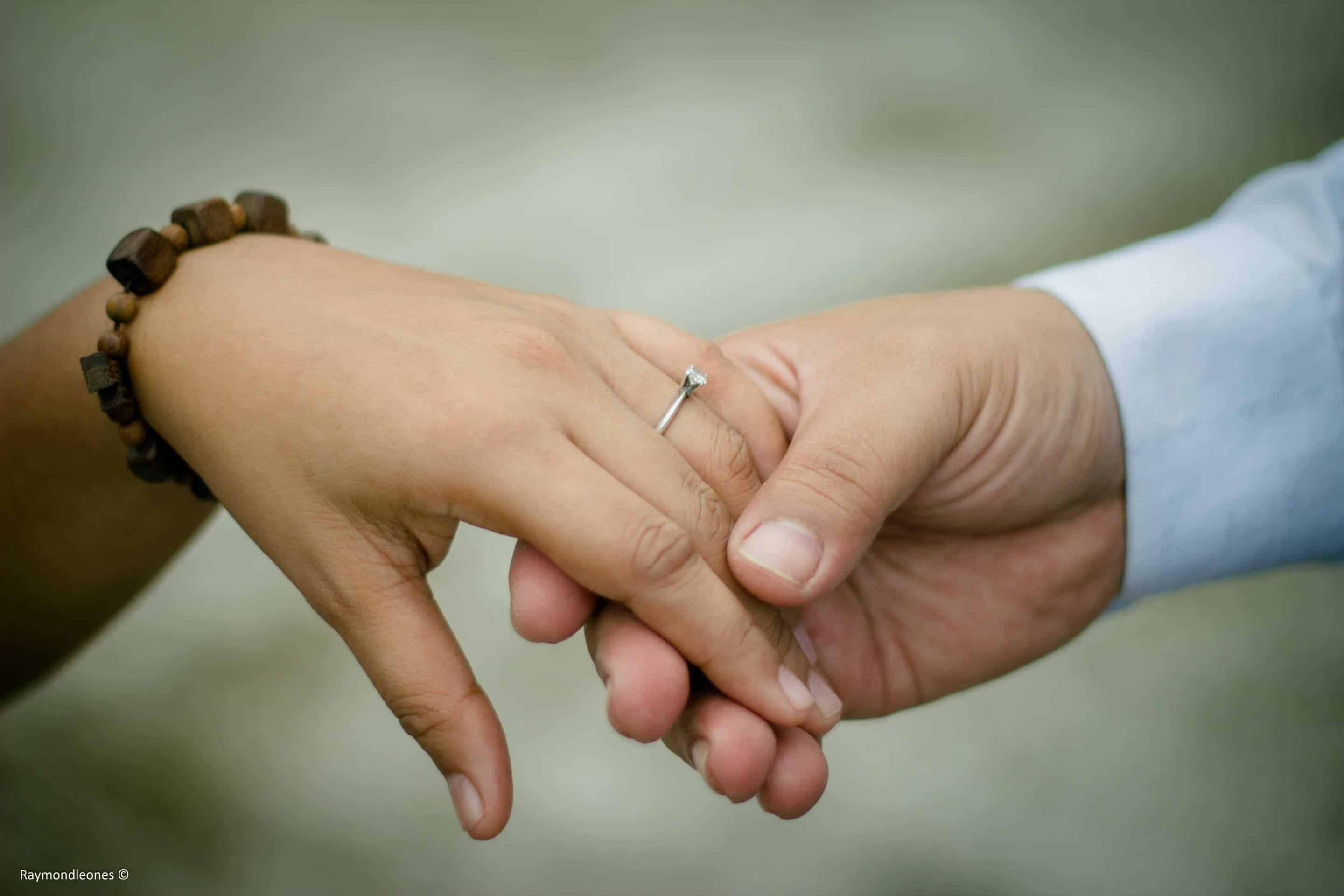 close-up picture of two hands holding each other with a visible engagement ring
